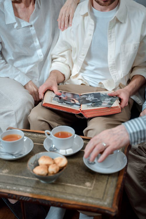 Three People Having Tea Time While Looking At Old Photos