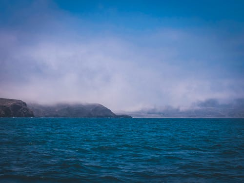Green Island on Blue Sea Under White Clouds and Blue Sky