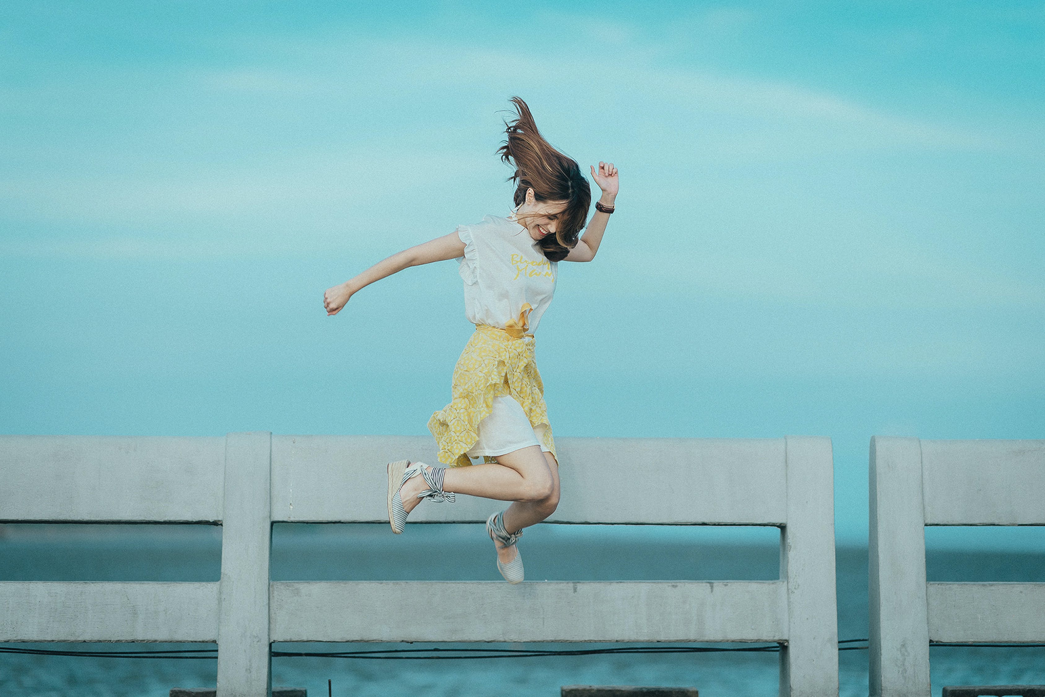 水域の近くの白と黄色のドレスを着た女性のジャンプショット写真