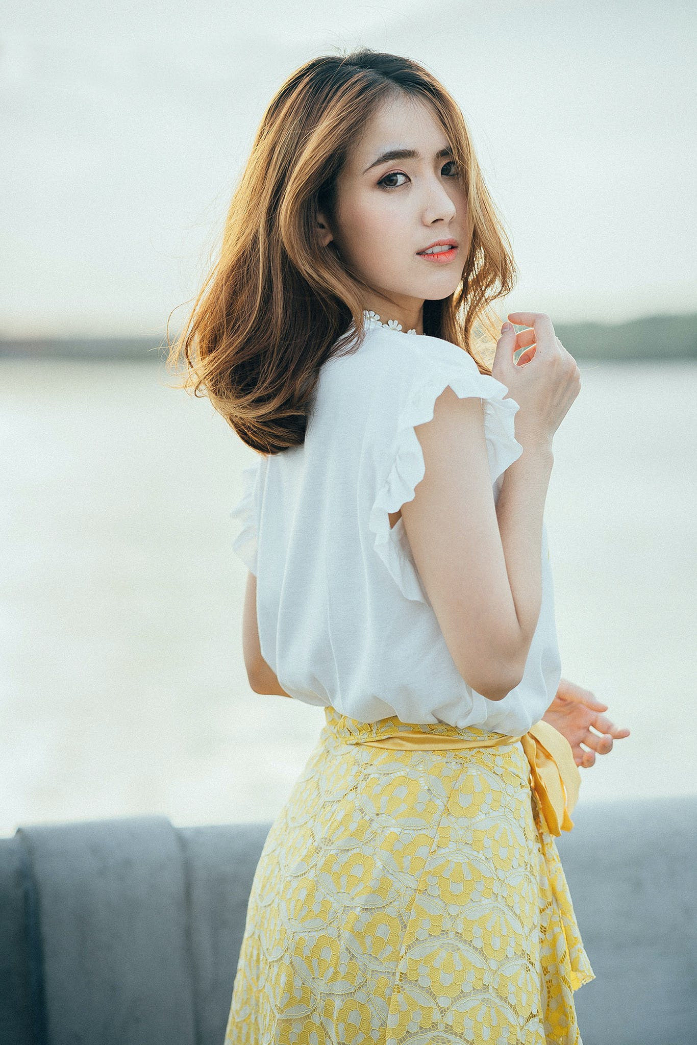 Photo of Woman Wearing White Sleeveless Shirt and Yellow Floral Skirt Near Body of Water