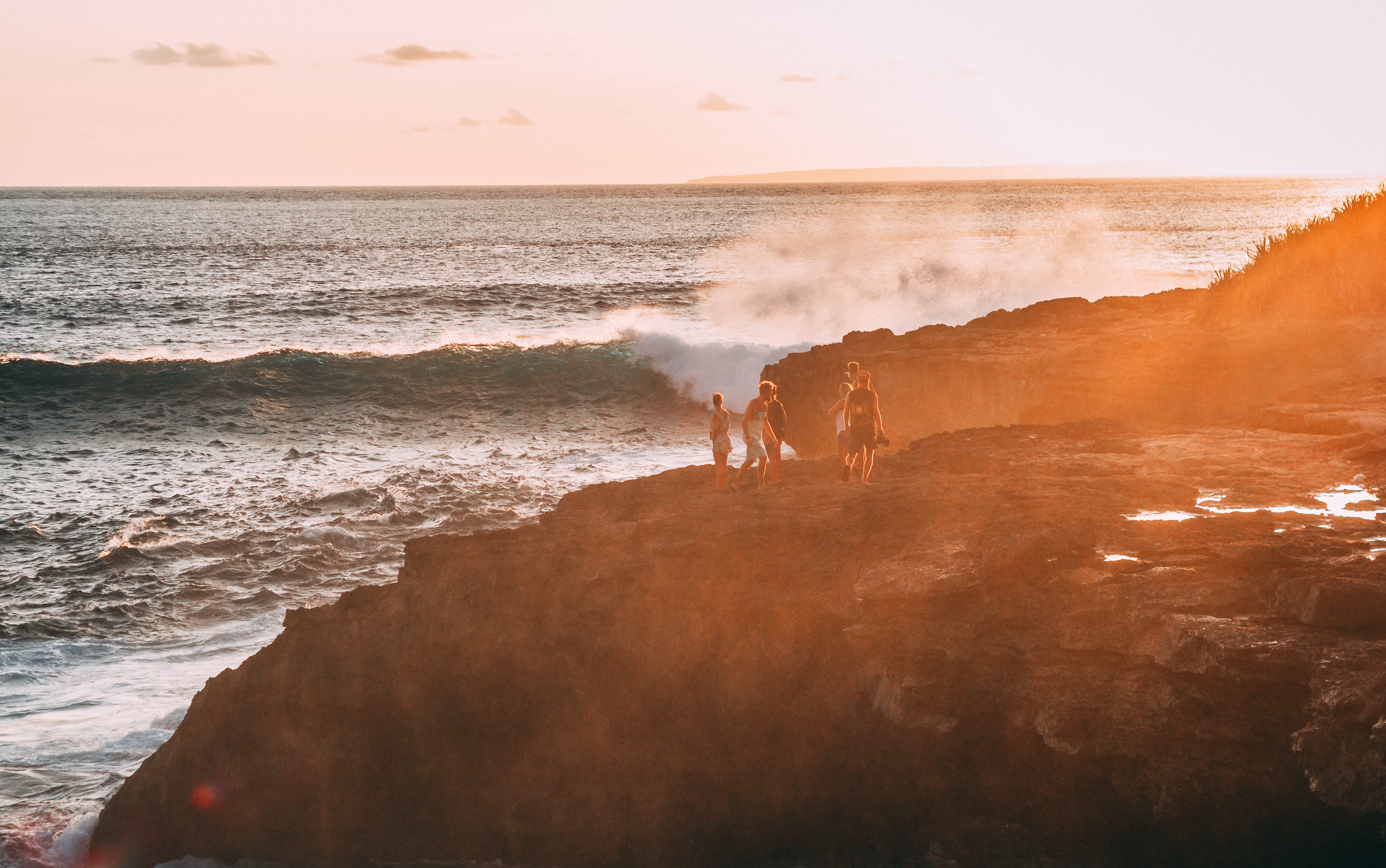 People Standing on Cliff Near Body of Water Golden Hour Photography