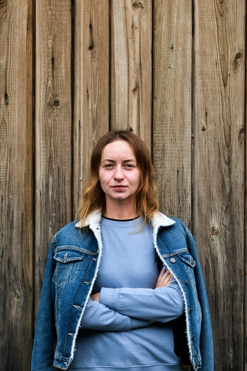Woman in Denim Jacket in front of Wooden Wall