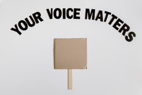 Gratis arkivbilde med din stemme betyr noe, flatlay, grå overflate