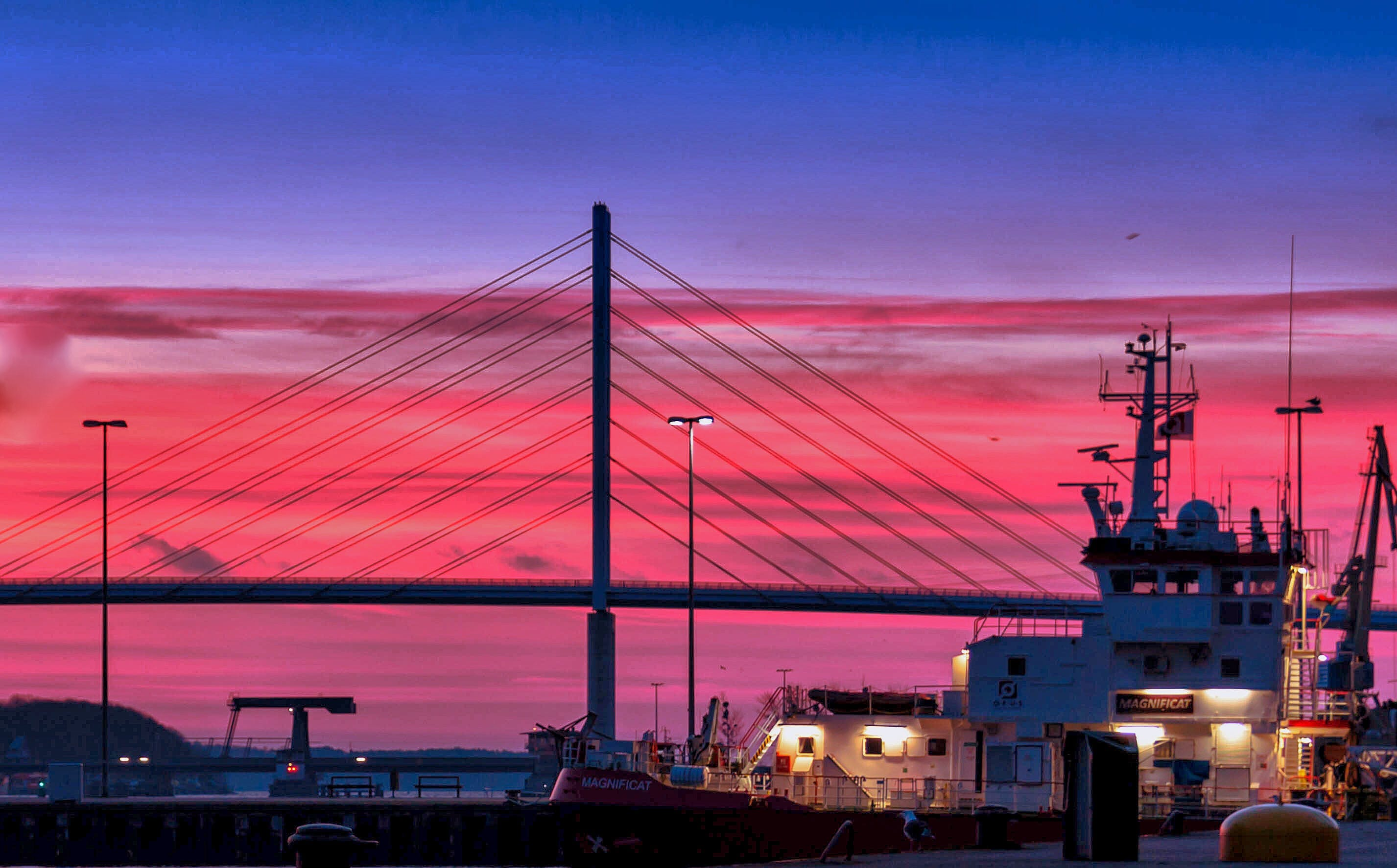 Silhouette of a Bridge Under Red Clouds and Blue Sky Taken during Night Time