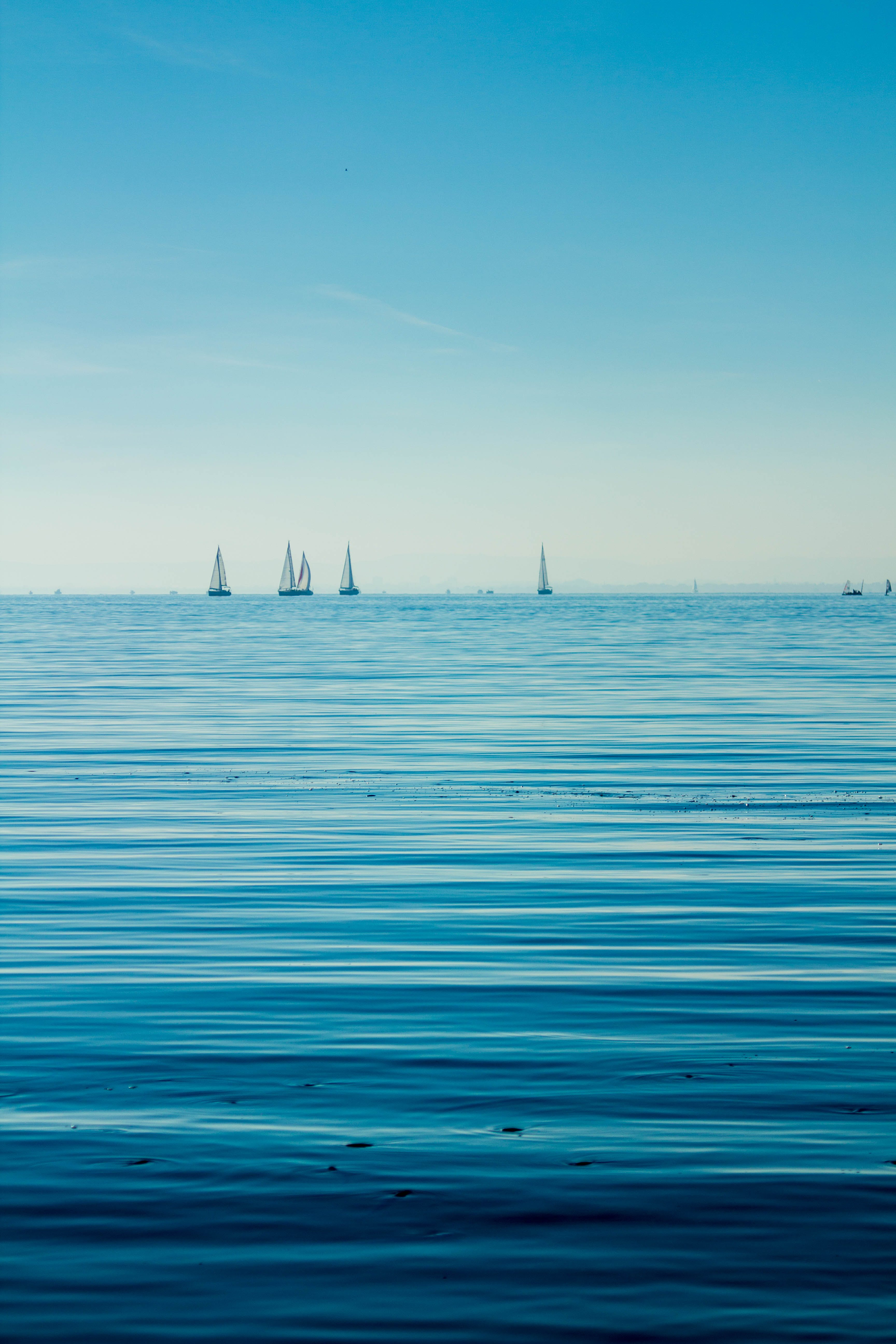 Boats on Body of Water Under Blue Sky