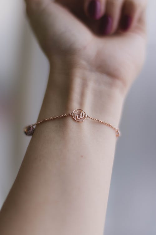 Person Wearing Pink Gold-colored Faith Bracelet