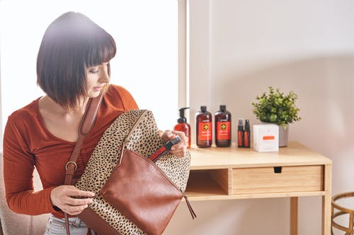 Woman in Brown and Black Leopard Print Coat Holding Coca Cola Bottle