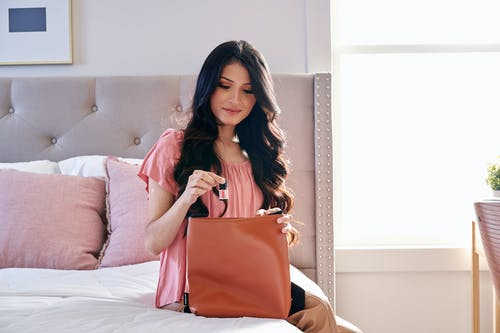 Woman in Pink Shirt Sitting on Bed Holding Red Leather Handbag