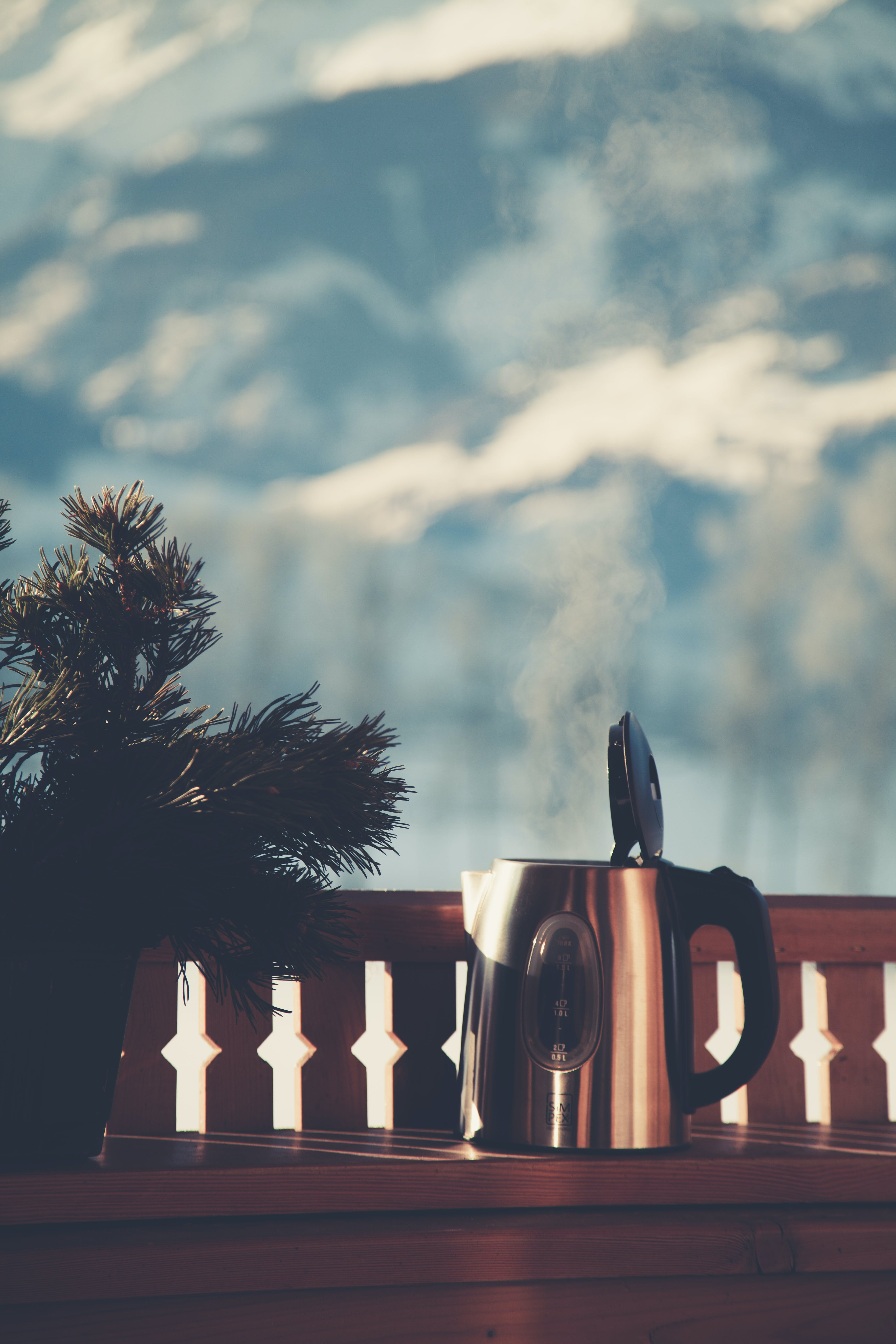 Selective Focus Photography of Silver Electric Kettle Beside Gray Balustrade
