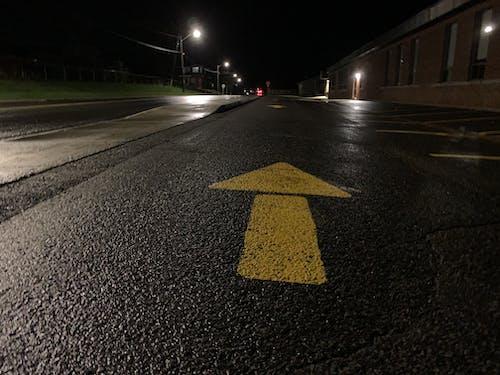 Free stock photo of arrow, asphalt road, light posts