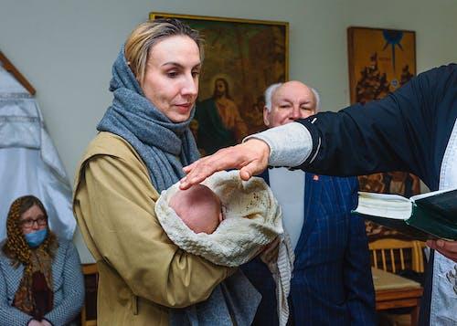 Gratis stockfoto met baby, doop, dragen