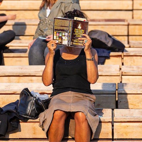 Foto profissional grátis de arquibancada, escondendo o rosto, livro