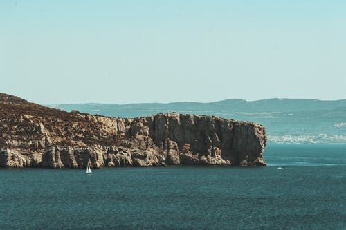 Gratis arkivbilde med bakgrunnsbilde, blå sjø, blått hav og oransje stein