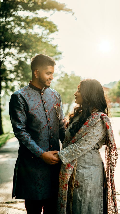Side view of romantic Indian couple wearing traditional outfits holding hands while standing on street with trees during wedding celebration