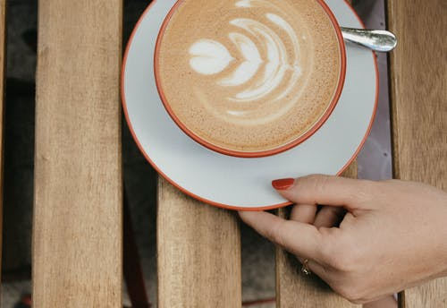 Person Holding a Saucer with a Cup of Coffee