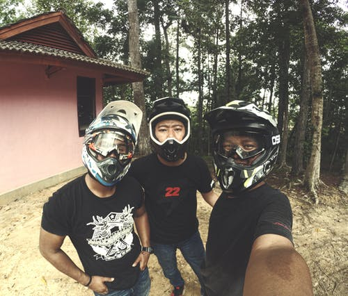 Three Men Wearing Helmet Standing Near House Outdoor
