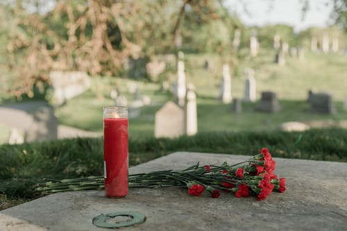 Red Candle and Flowers On A Tomb