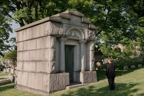 Woman In Black Outfit Standing In Front Of A Mausoleum