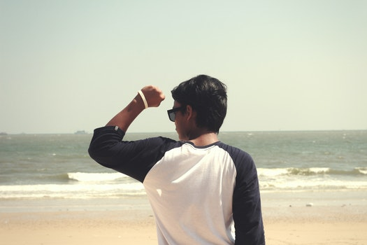Man in White and Black Raglan Shirt Standing in the Seashore at Daytime
