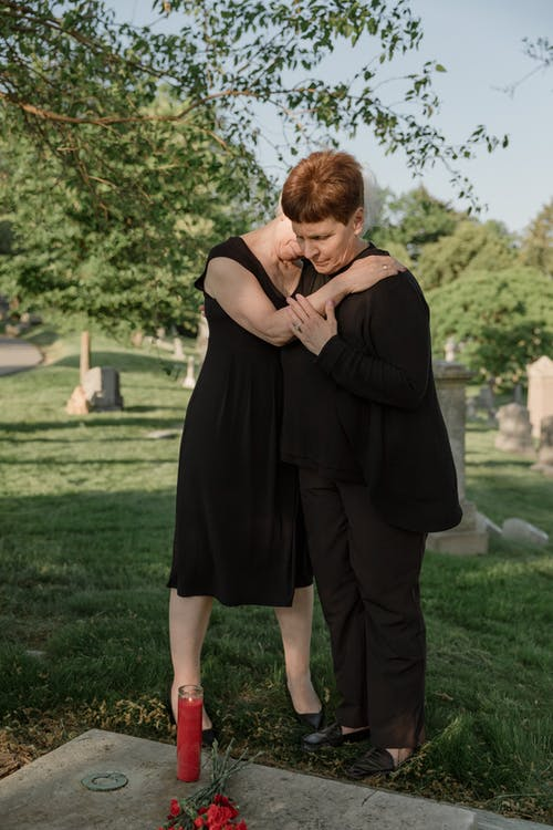 Two Grieving Women Standing In Front Of A Grave