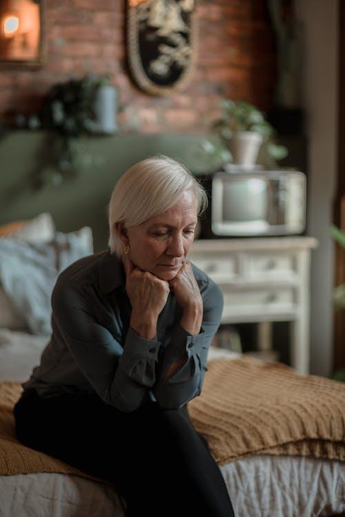 Elderly Woman Sitting On Bed Feeling Sad