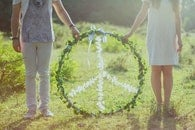 Two Person Holding White and Green Peace Wreath