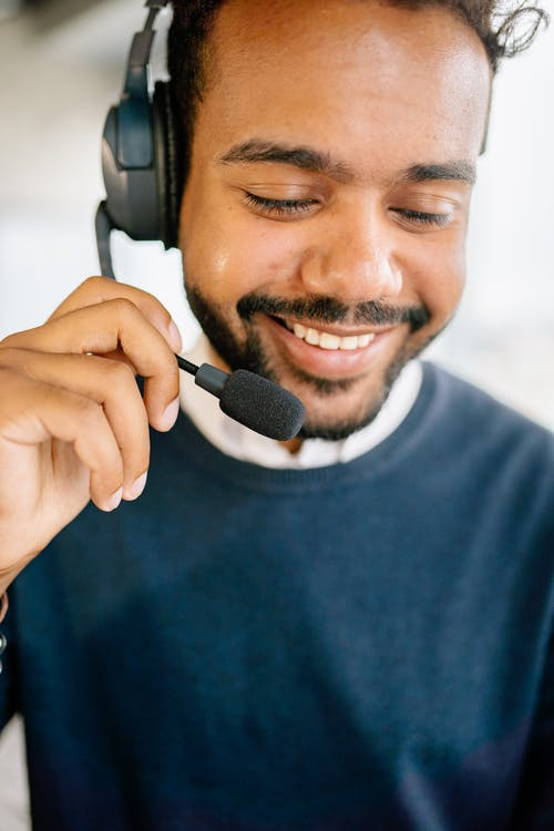 Man in Blue Crew Neck Shirt Holding Black Headset Microphone