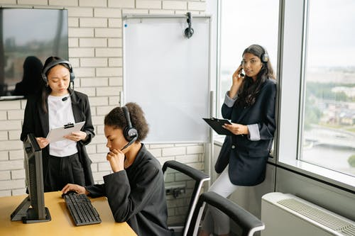 Three Women in Black Blazers With Headsets Working As Customer Support Agents