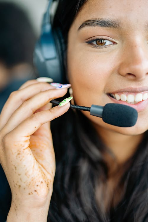 Close-Up Photo of a Woman Using a Black Headphones