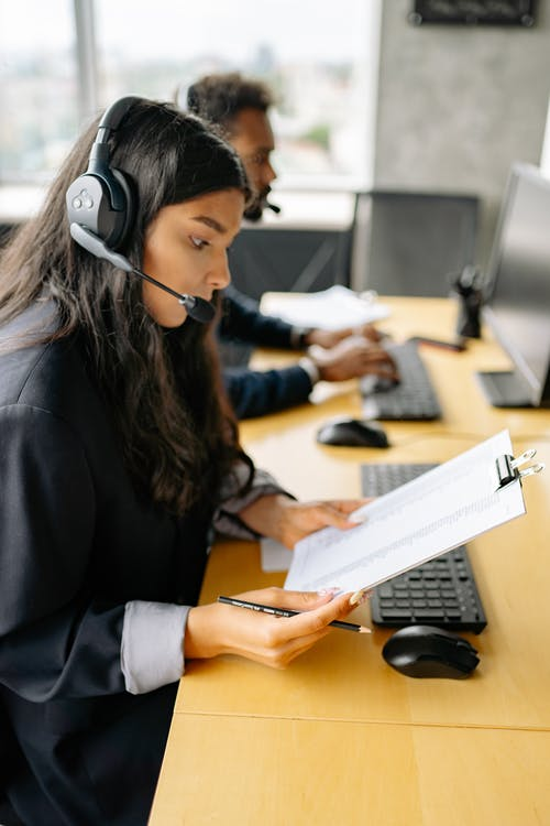 A Woman Working in a Call Center while Looking at a Document