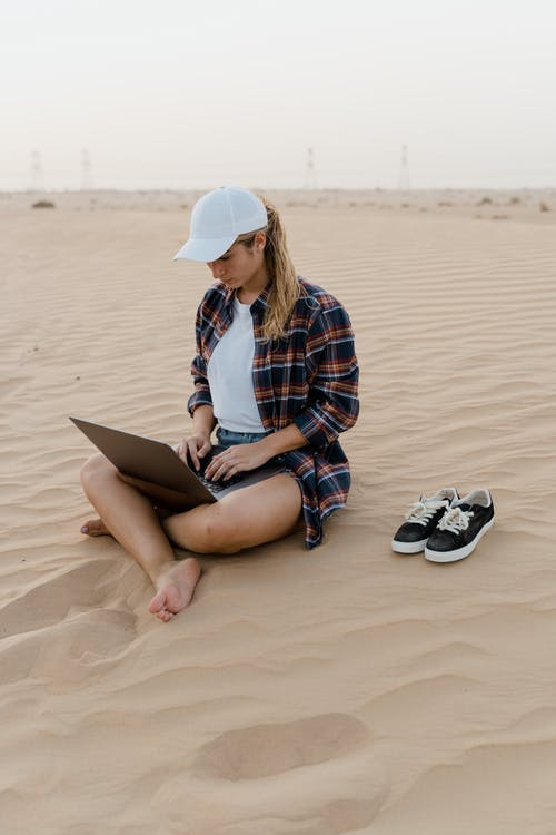 Woman in Blue and White Plaid Dress Shirt Using Macbook on Sand