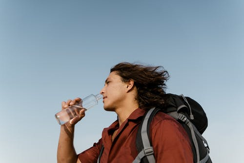 Man Drinking from Clear Glass Bottle