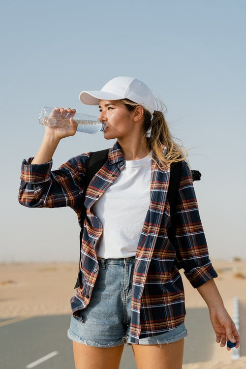 Woman in White Shirt and Red Black Plaid Coat Drinking Water