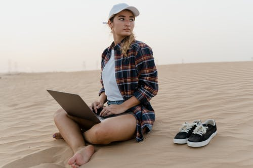 Woman in Blue White and Red Plaid Dress Shirt Sitting on Brown Sand Using Macbook