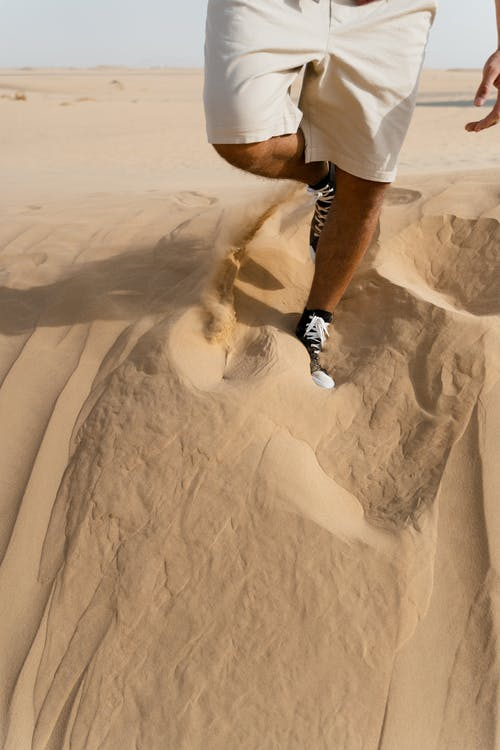 Person in White Shorts and Black Sneakers Standing on Sand