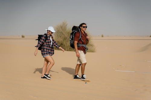 2 Women Walking on Brown Sand