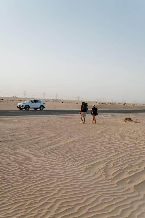 2 Men Standing Beside White Car on Brown Sand