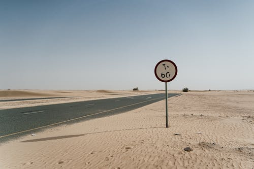 White and Black No Parking Sign on Brown Sand