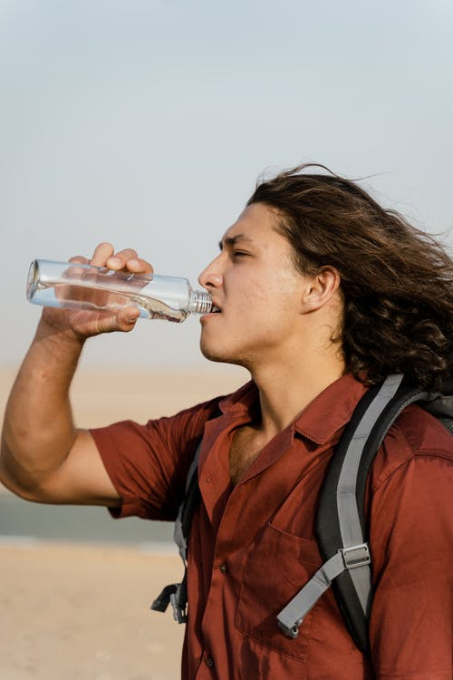 Woman Drinking from Clear Glass Bottle