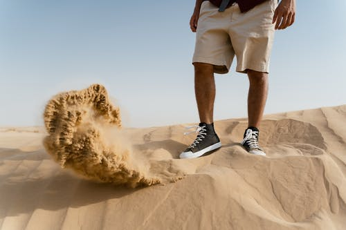 Person in Black and White Adidas Sneakers Standing on Brown Sand