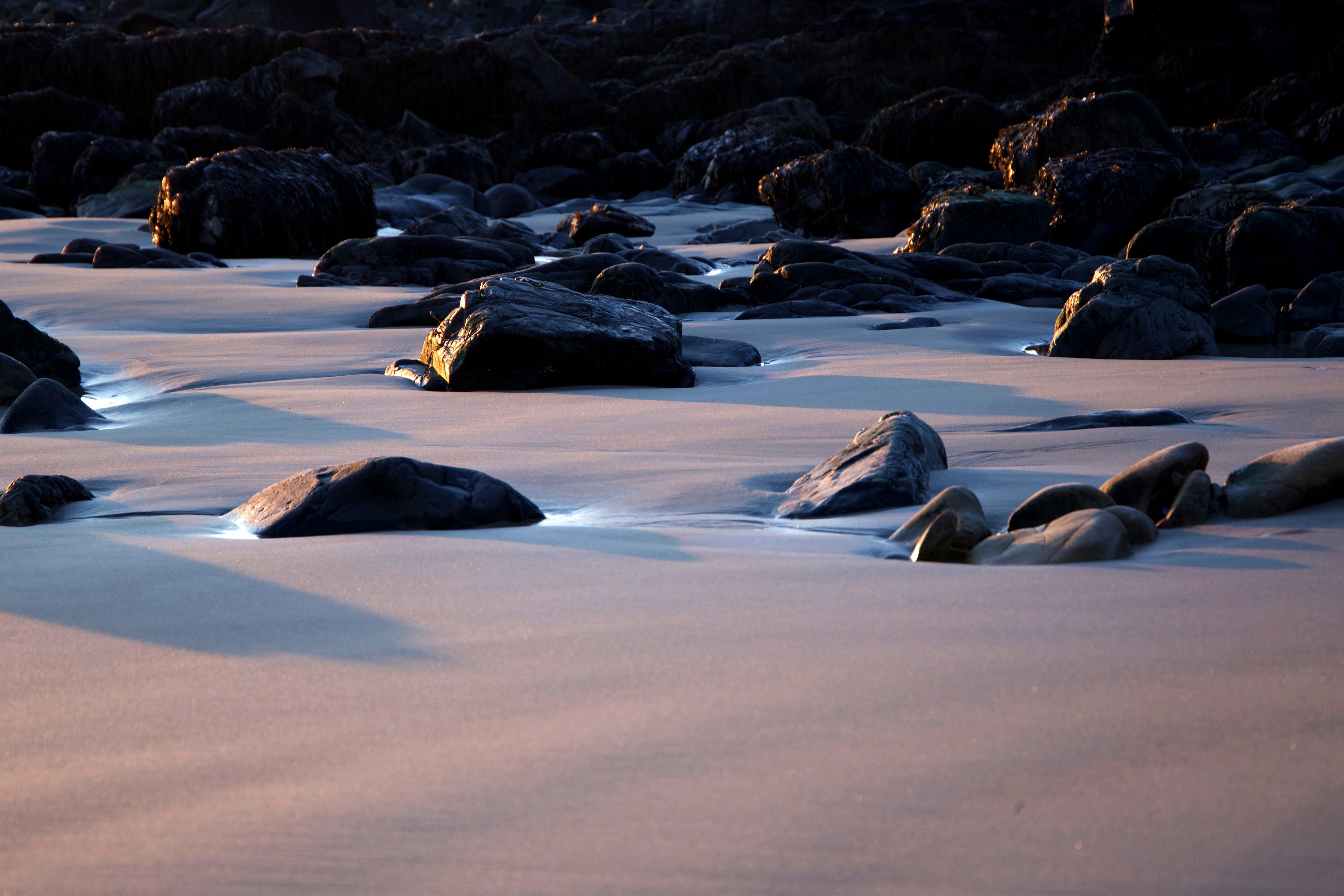 Black Rocks on Sand during Daytime