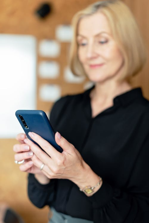 Woman in Black Dress Up Shirt Holding A Blue Smartphone