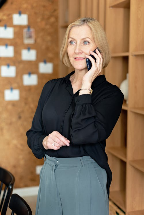 Woman in Black Dress Up Shirt and Gray Trousers Using Cellphone