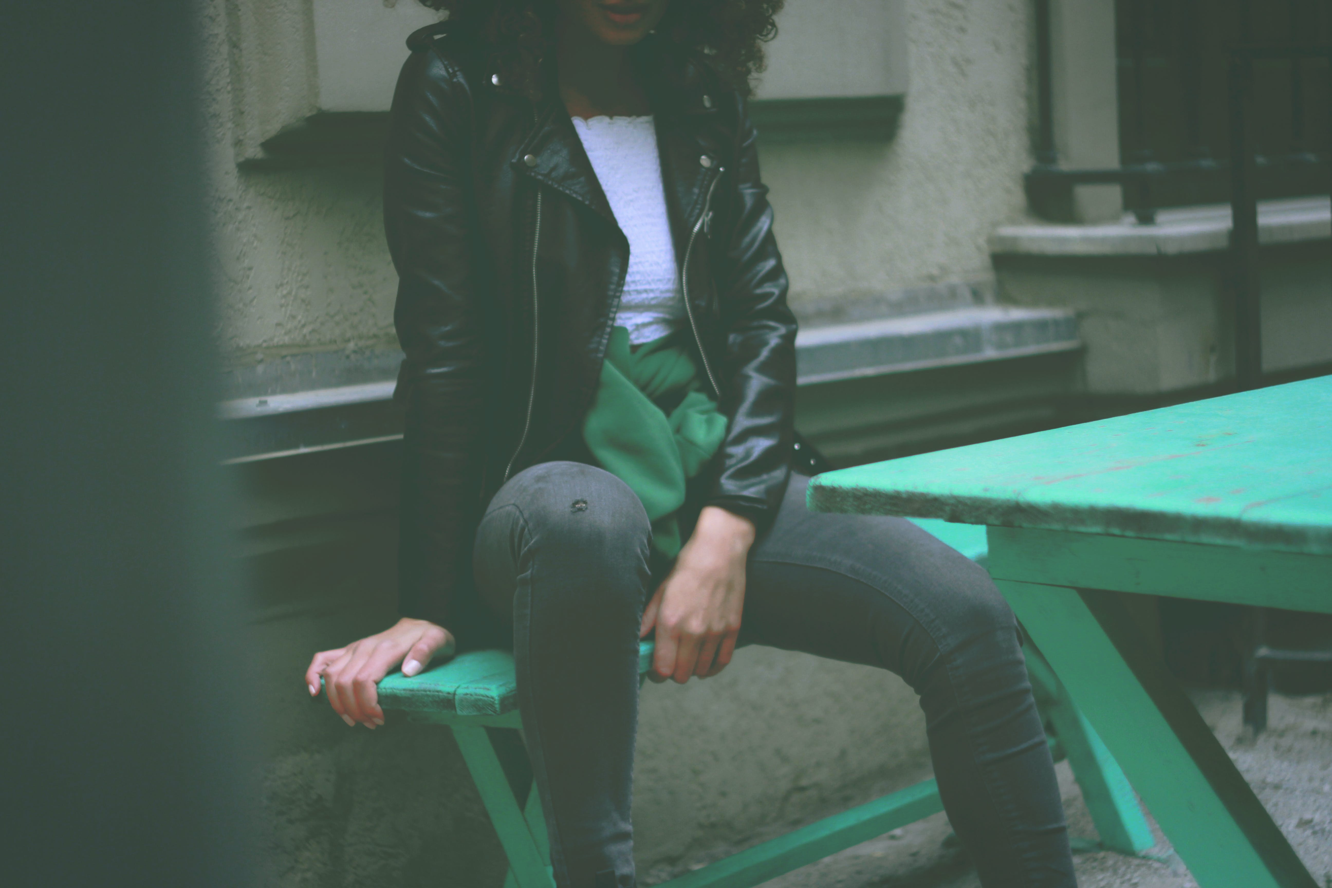 Woman Wearing Black Leather Jacket Sitting on Green Wooden Bench