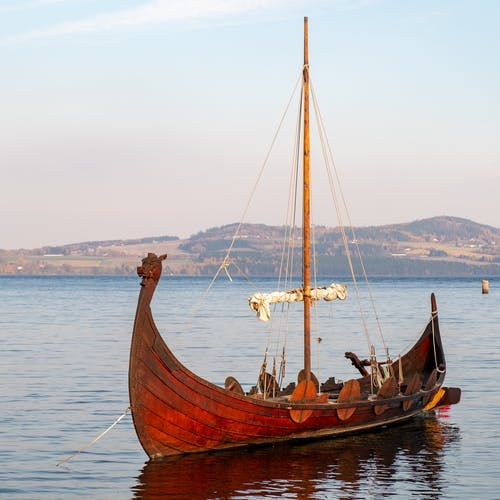 Brown Wooden Boat on Sea