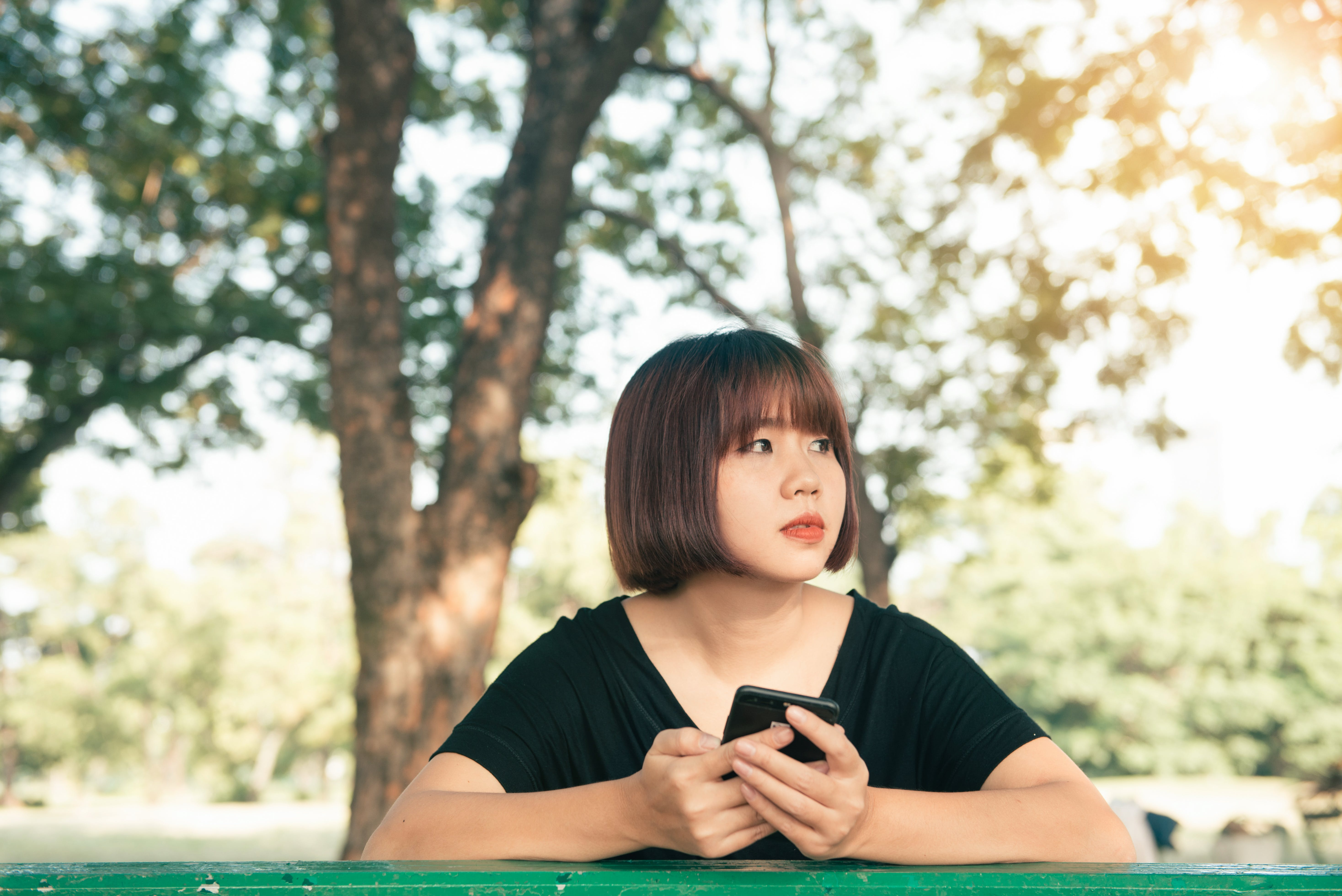 Woman Holding Smartphone Wearing Black Shirt Standing Under Tree