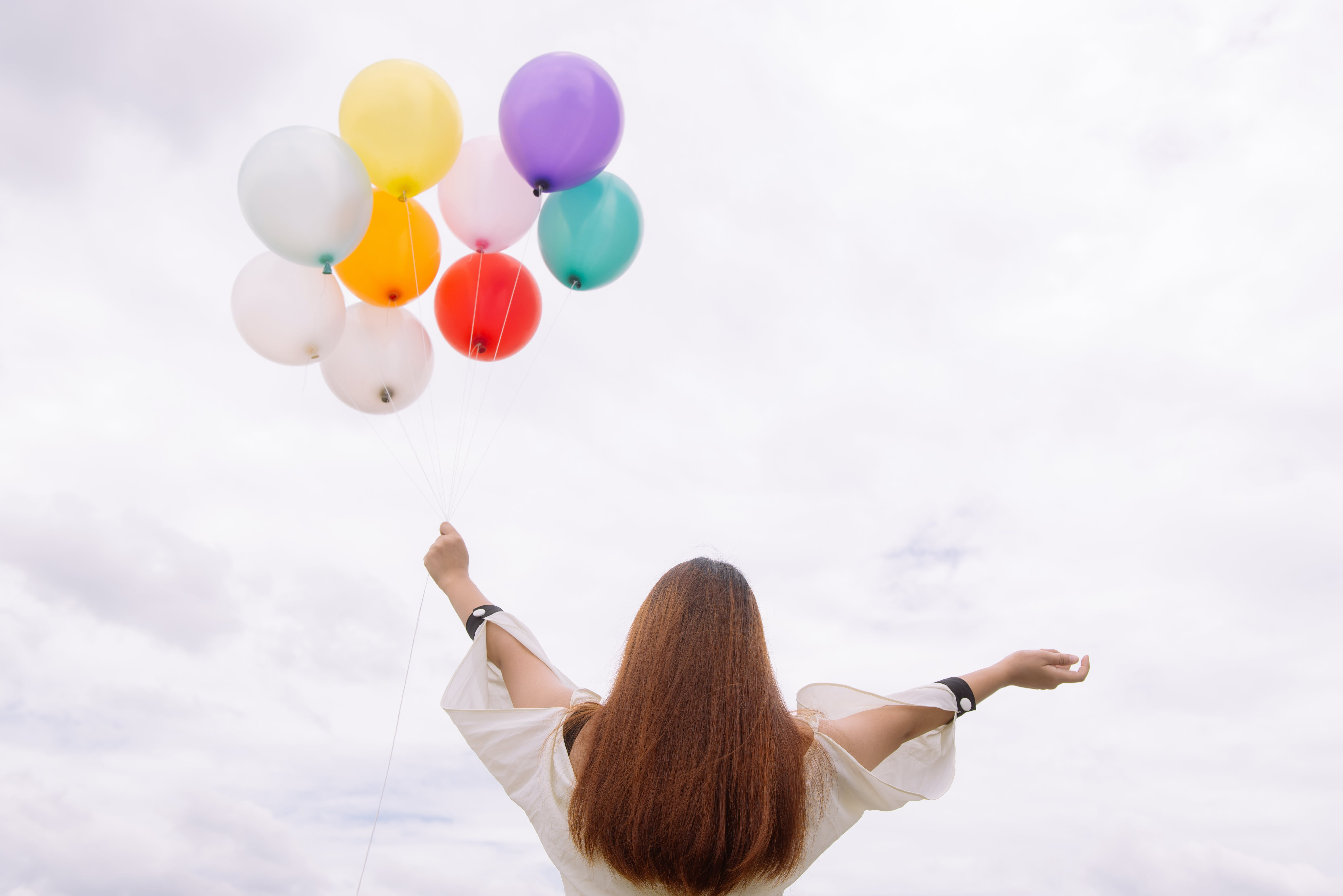 Worm's-eye View of Woman Holding Balloons