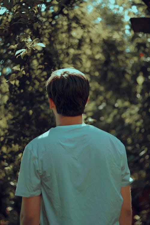 Man in White Crew Neck Shirt Standing Near Green Tree