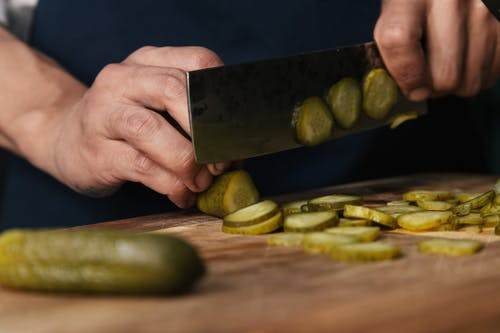 Person Slicing Pickles on a Wooden Chopping Board