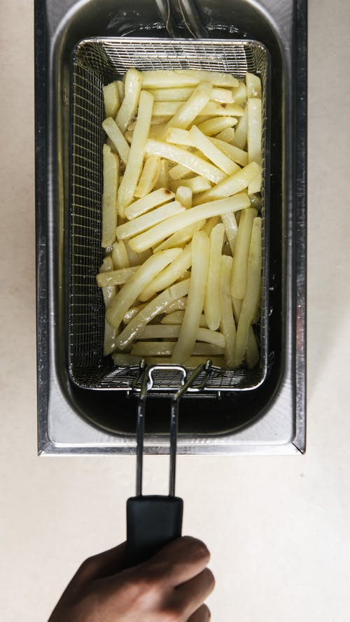 Close-Up Shot of a Person Frying French Fries